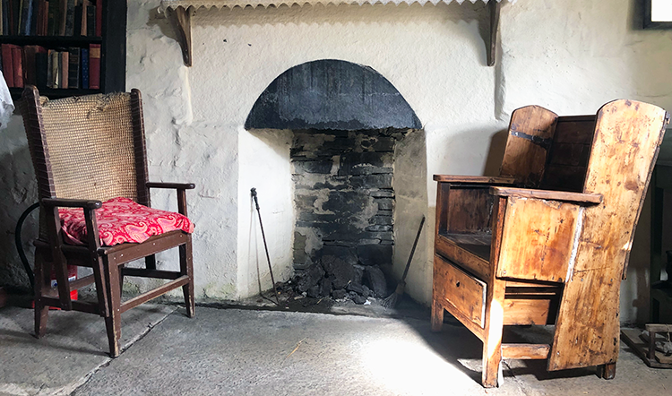 A typical Orkney chair sits next to a traditional fireplace, with a central peat fire
